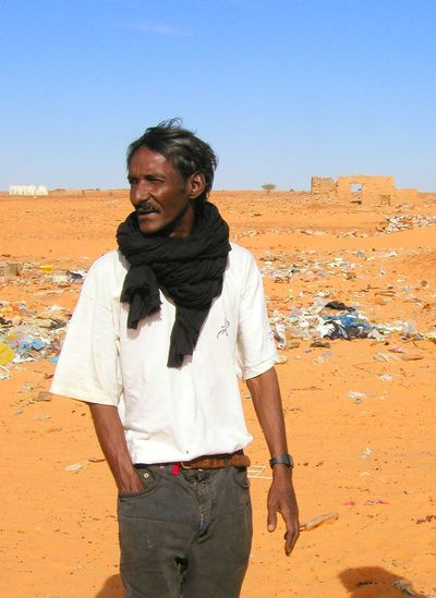 Cheikh Day Desert Front View Lifestyles Men Nature One Person Outdoors Real People Sahara Sand Sky Standing Sunlight Three Quarter Length Trash