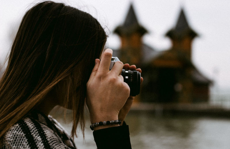 young woman photographing with old vintage zenit camera One Person Headshot Long Hair Photography Themes Photographing Hairstyle Focus On Foreground Hair Women Leisure Activity Portrait Activity Lifestyles Technology Real People Adult Camera - Photographic Equipment Rear View Holding Digital Camera