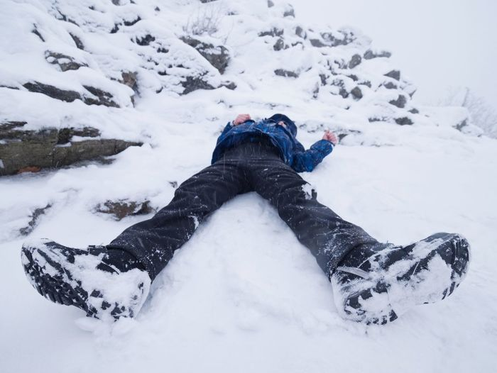 Person lying on snow covered land