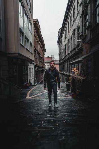 Man standing on wet street amidst buildings