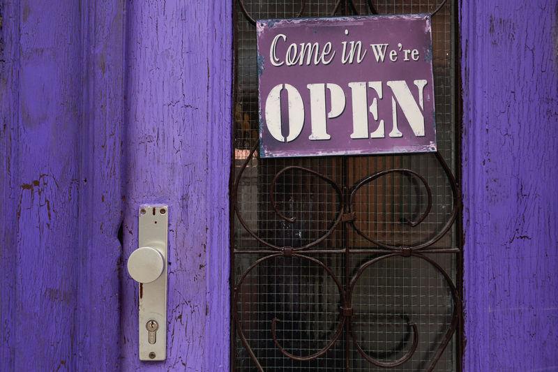 Open sign hanging on purple door