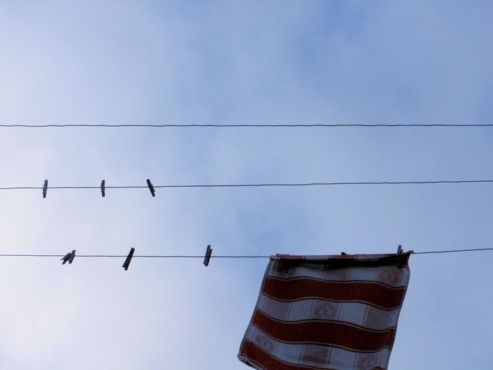 Low Angle View Of Clothesline Against Blue Sky