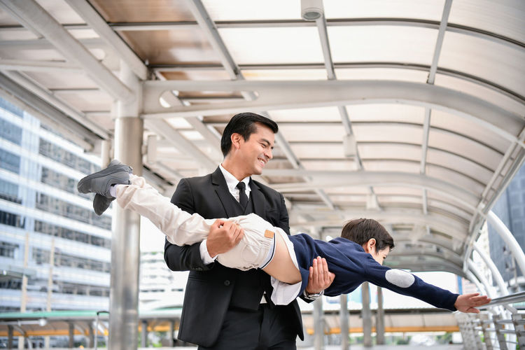 Father carrying son as airplane in city