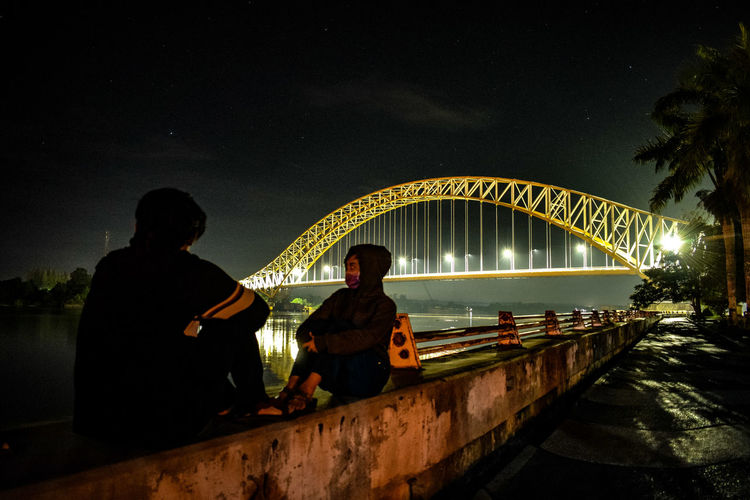 People sitting on bridge over river against sky at night