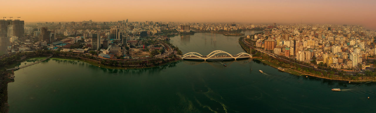 Aerial view of bridge over river and buildings against sky during sunset