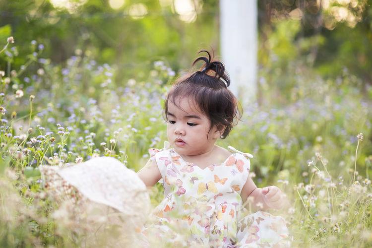 Cute girl looking at flowering plants