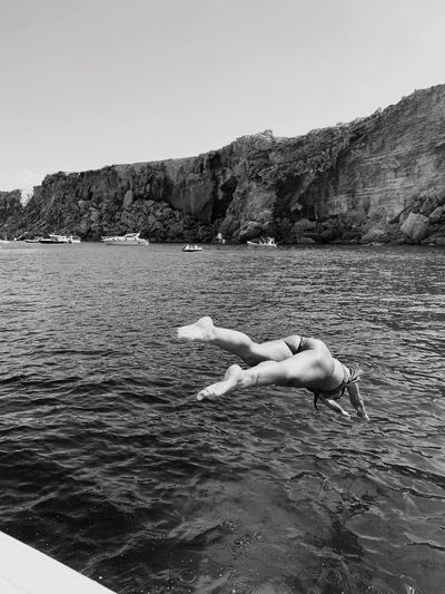 Woman diving into sea against clear sky