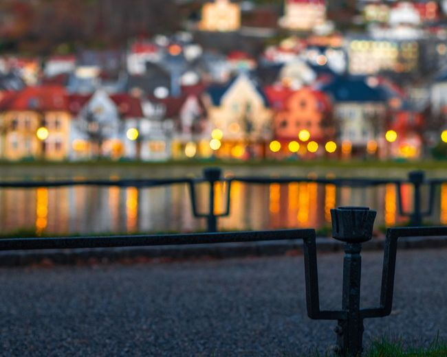 Illuminated railing by river in city at night