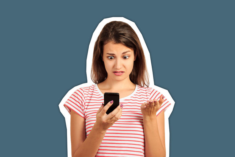 Portrait of a young woman using phone against blue background