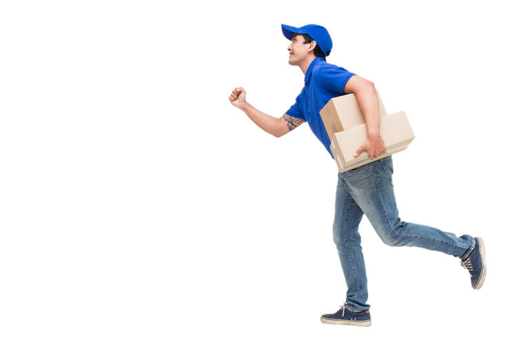 Salesman with cardboard boxes running against white background