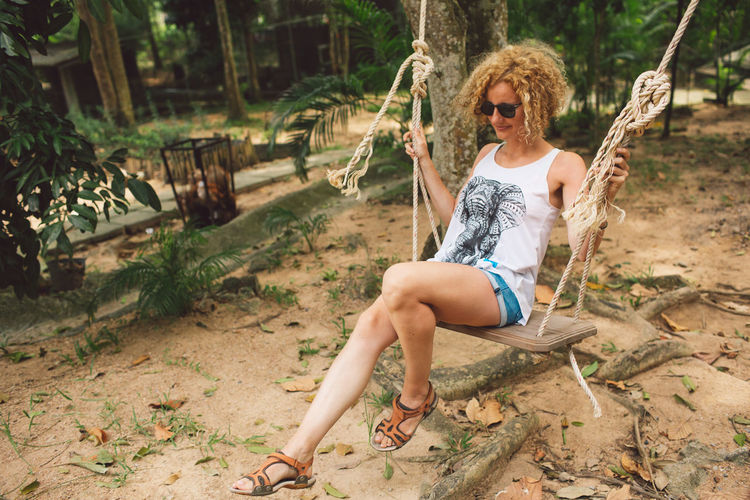 Curly Hair Girl Full Length One Person Real People Sitting Leisure Activity Casual Clothing Young Adult Lifestyles Nature Day Young Women Front View Fashion Holding Sunglasses Land Glasses Tree Outdoors Hairstyle Shorts Beautiful Woman Contemplation