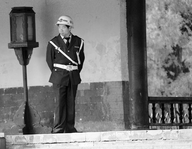 Full length of man wearing uniform while standing against wall
