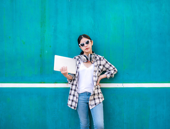 Young woman with laptop and headphones standing against blue wall