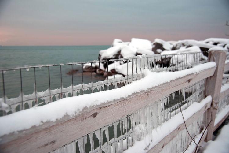 Close-up of snow on railing by sea against sky