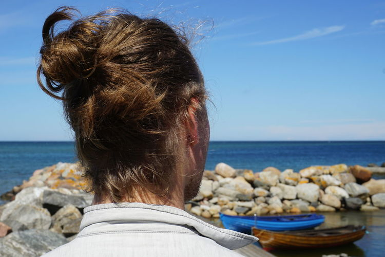 Rear view of man at beach against sky