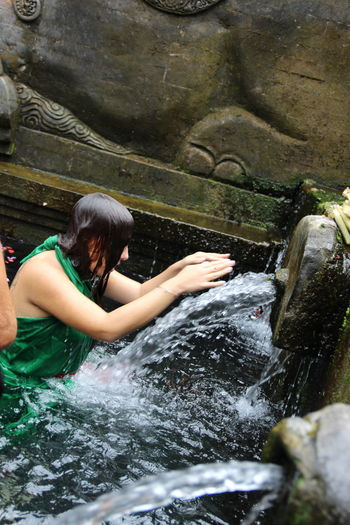 Purification ritual at the Tirta Empul temple Hinduism Ritual Adult Child Day Flowing Water Leisure Activity Lifestyles Motion Nature One Person Outdoors Purification Real People Rock Rock - Object Solid Splashing Three Quarter Length Water Waterfront Women