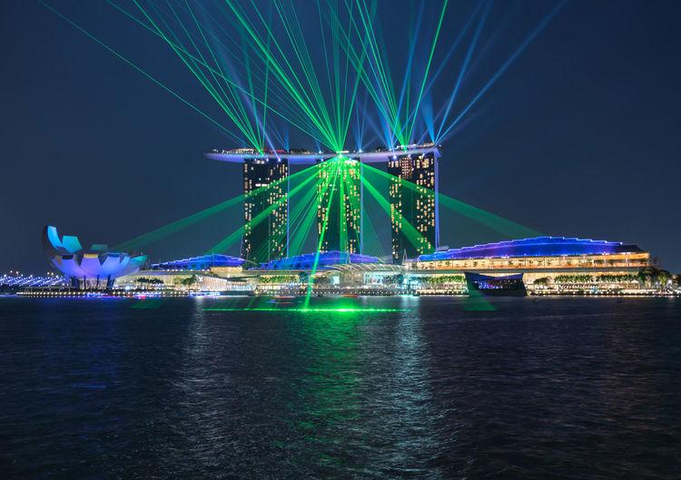 Laser Light Display On Illuminated Marina Bay Sands By Sea At Dusk