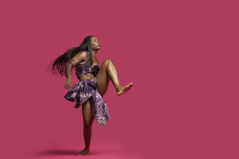 Beautiful African Black girl wearing traditional colorful African outfit does a dramatic dance move against a colorful pink background African African Traditions Adult African Dancer African Woman  Beautiful People Beautiful Woman Beauty Clothing Colored Background Dandelion Fashion Females Full Length Glamour Hair Hairstyle Human Limb Indoors  Limb Lingerie Long Hair One Person Pink Color Studio Shot Tradition Dress Women Young Adult Young Women