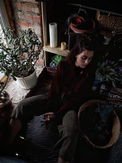 Portrait of young woman sitting on potted plant at home