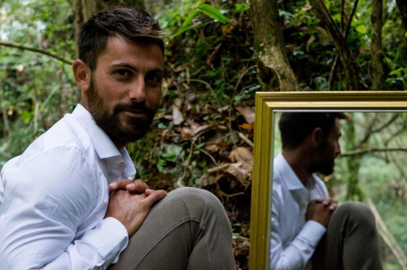 Portrait of young man with reflection on mirror at forest