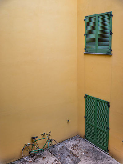 Window Blind Emptiness Loneliness Shutters Architecture Bicycle Building Exterior Built Structure Day Green Shutters Green Window Minimalism No People Outdoors Yellow Walls