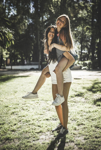 Full Length Portrait Of Woman Piggybacking Friend On Field At Park
