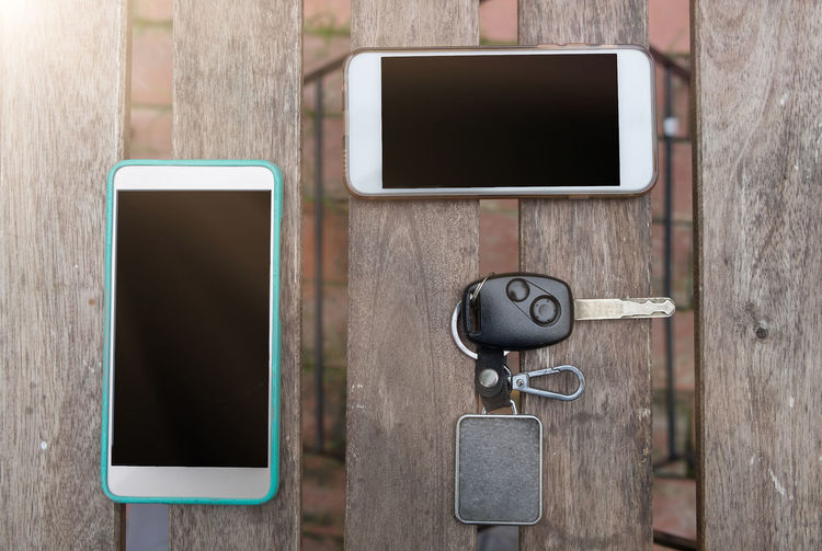 Directly above shot of smart phones and car key on wooden table