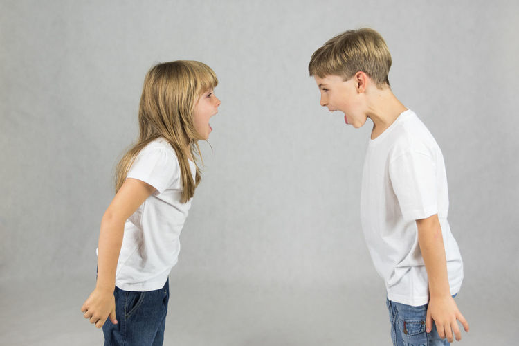 Young children fighting and shouting at each other Anger Arguing  Blond Hair Boys Casual Clothing Child Childhood Conflict Day Elementary Age Girls Gray Gray Background Indoors  People Scolding Standing Studio Shot Two People White Background