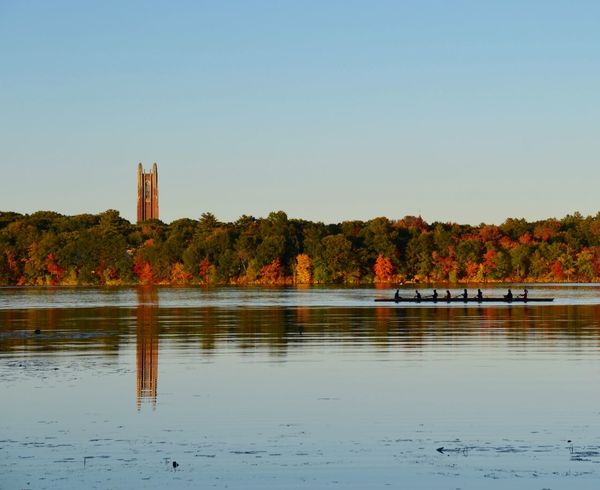 Wellesley students rowing on Lake Waban, with Galen Stone Tower in the background, reflecting off the lake. October 2015. Architecture Autumn Built Structure Clear Sky Colors Of Autumn Crew Lake Nature Reflection Reflection Rowing Scenics Sunset Tower Water Wellesley College