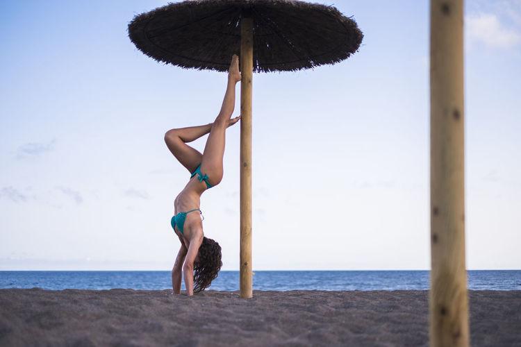 Woman wearing bikini doing handstand at beach against sky