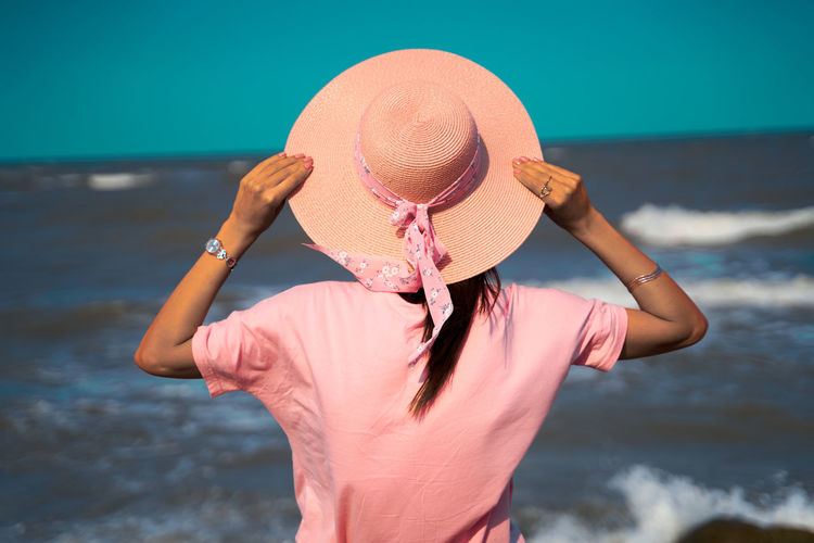 Midsection of woman wearing hat while standing on beach