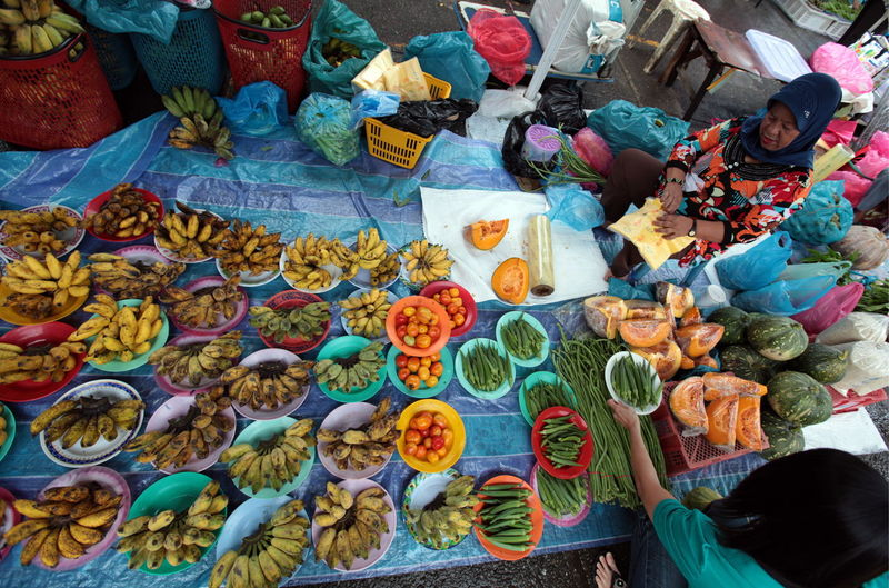 High angle view of woman buying vegetable from female vendor at market
