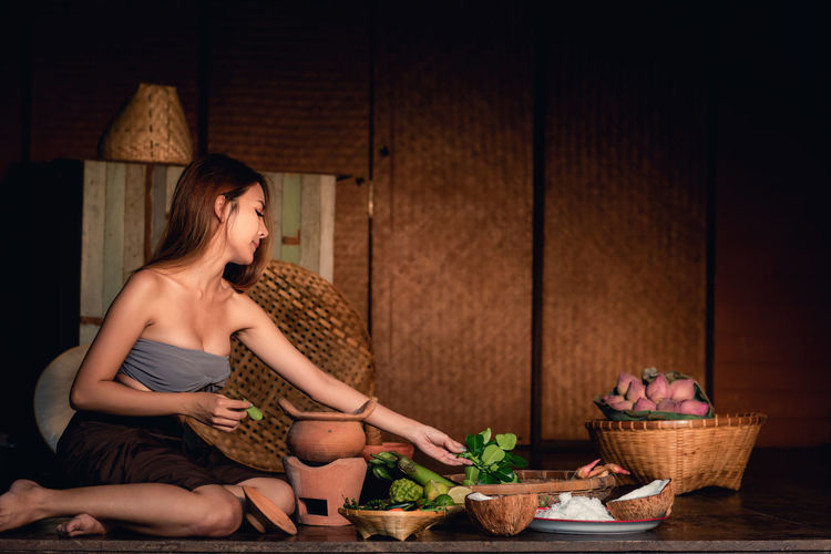 Thai woman is providing ingredient for cooking in the evening., Thai cultural. Food And Drink Sitting Food Basket Indoors  Women Lifestyles Real People Container Young Women Adult Table Freshness Casual Clothing Vegetable Hairstyle Beautiful Woman Cooking Asian  Asian Food Ingredient Food Ingredients Vintage Thai Thailand