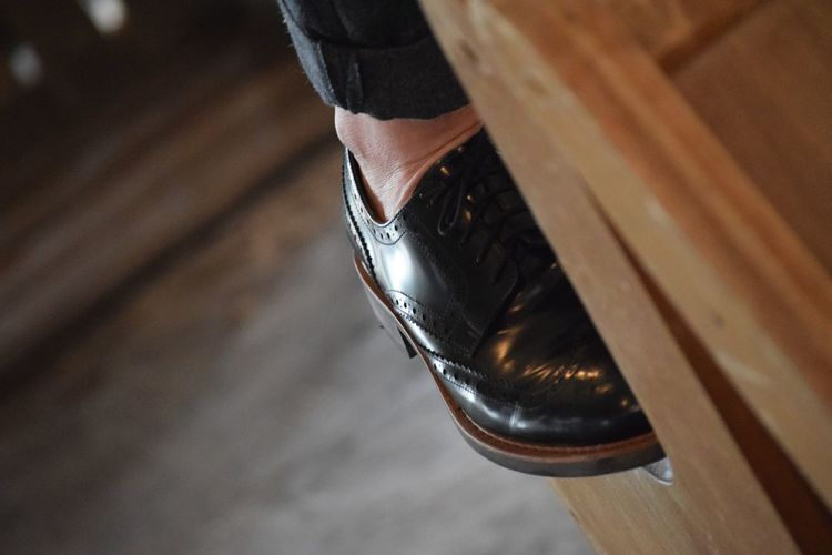 Low section of man wearing shoe on table at home