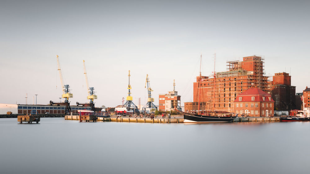commercial dock by sea against clear sky Architecture Building Exterior Built Structure City Cityscape Day Drilling Rig Fine Art Freight Transportation Industry Long Exposure Mecklenburg-Vorpommern Muted Colors No People Oil Industry Outdoors Philipp Dase Sea Sky Water Waterfront Wismar Wismarhafen