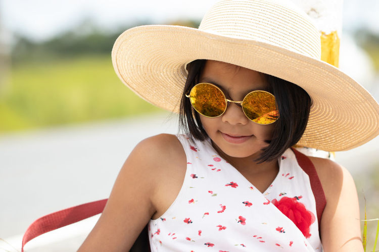 Close-Up Of Girl Wearing Sunglasses And Hat While Sitting Outdoors