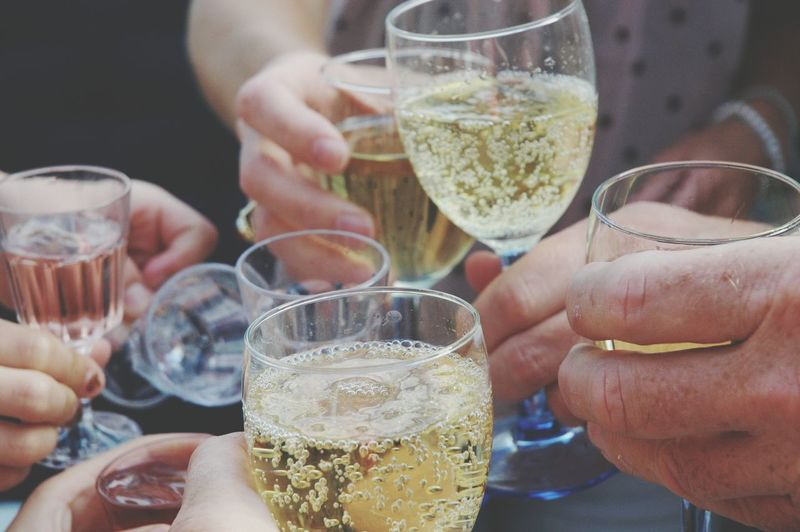 Close-up of people holding champagne and making a toast