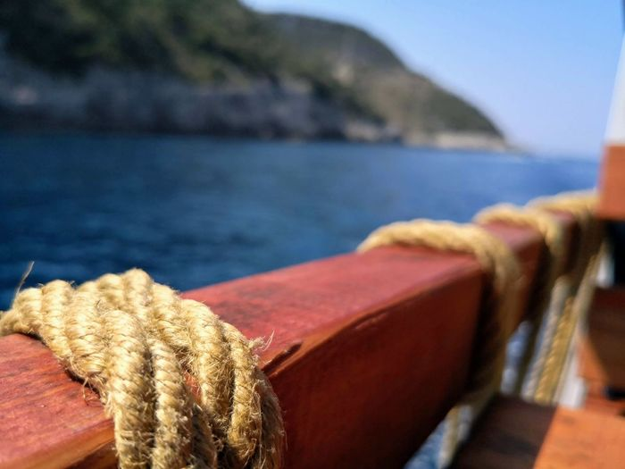 Close-up of rope tied on wood against sea
