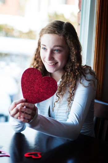 Young woman holding valentine heart