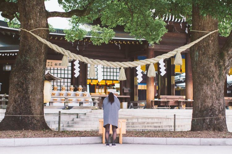 Rear View Of Woman Standing In Front Of Shinto Shrine