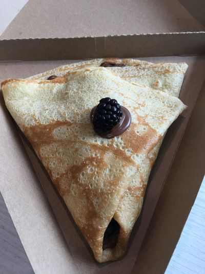 High angle view of crepe with chocolate and blackberry on box