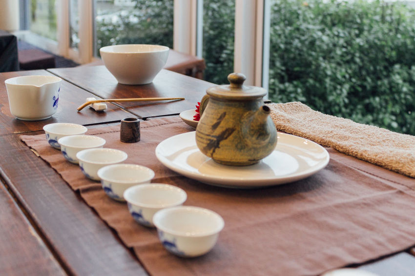 Chinese Tea Ceremony Bowl Brown Chinaware Chinese Culture Chinese Tea Close-up Cup Day Domestic Life Drink Food And Drink Freshness Indoors  No People Plate Porcelain  Pot Table Tablecloth Tea Tea Ceremony Tea Cup Tree Window Wood - Material
