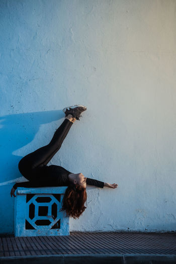 Full length of woman lying down by wall outdoors