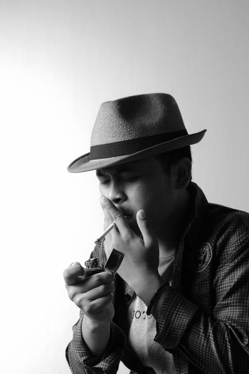 Man igniting cigarette against white background