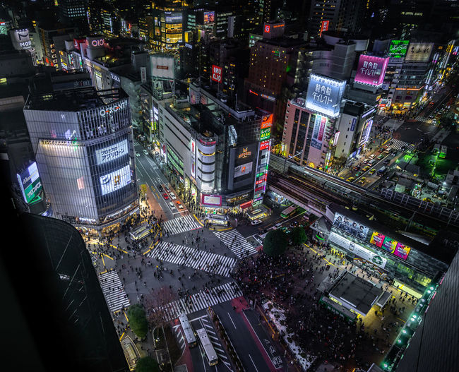 High angle view of illuminated city street and buildings at night