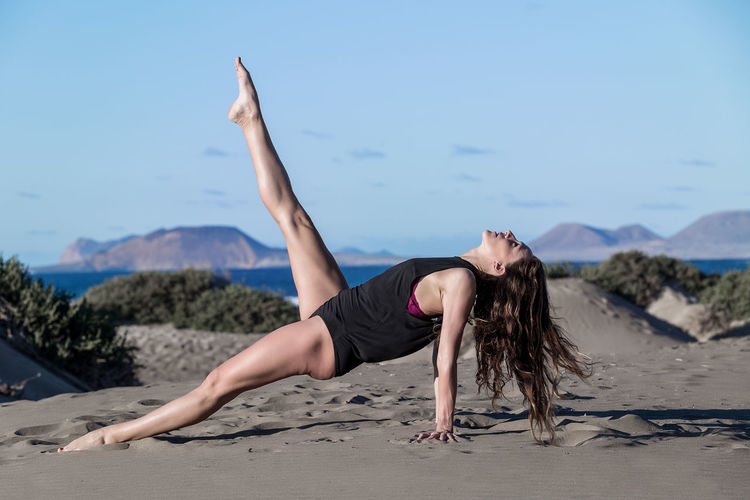 Full length of woman practicing yoga at beach against sky