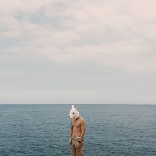 Man In Dog Mask Standing By Sea Against Sky