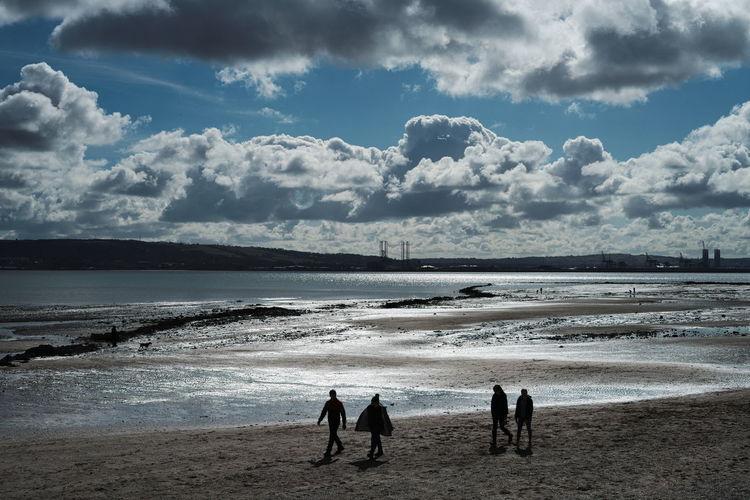 Silhouette people walking at beach against sky