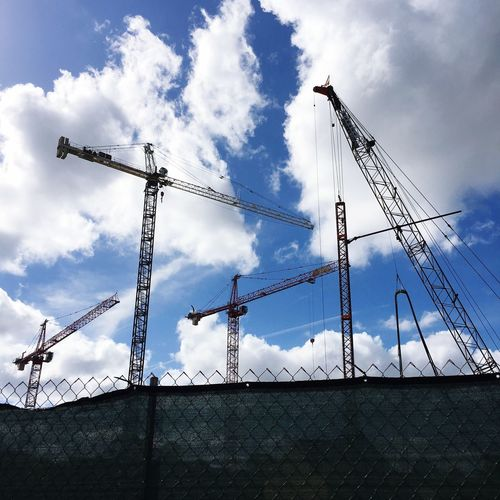 Low angle view of cranes against clouds