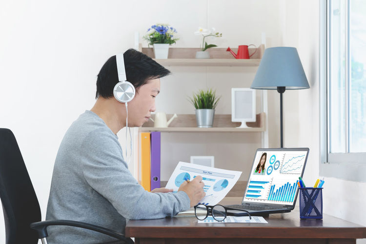 Midsection of man using laptop while sitting on table